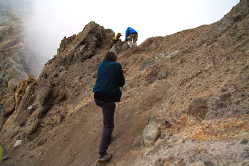 Pulling ourselves up rope on side of cliff in Mutnovsky Volcano crater