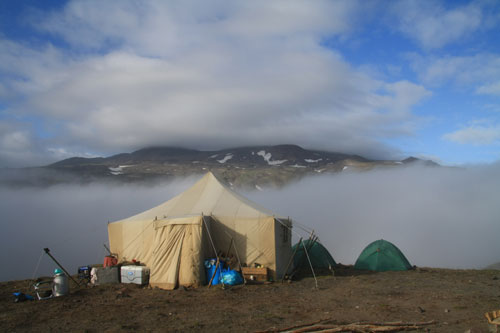 Cook Tent at camp with Gorley Volcano in clouds and volcanic steam plume behind