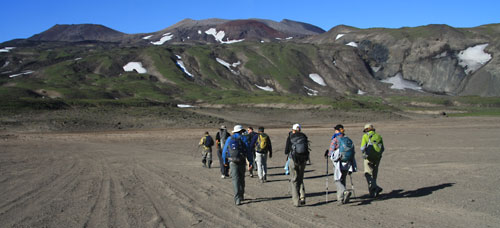 Crossing dry lake bed to start climb of Gorely Volcano (rim is directly in center of photo)