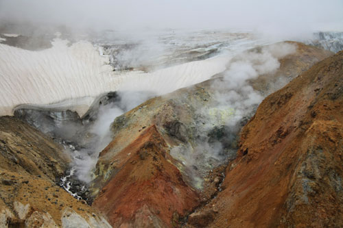 Fumaroles (steam vents) below hanging glaciers in Mutnovsky Volcano crater