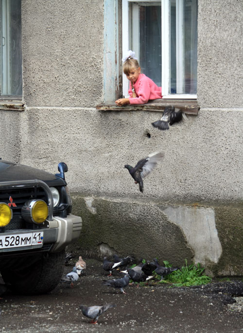 Young girl feeding pigeons in Petropavlovsk