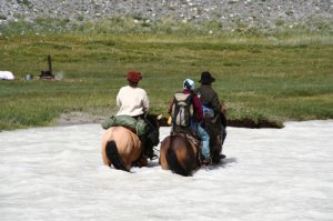 Crossing deep glacial river in Mongolia on horseback