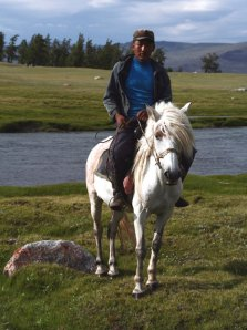 Young Mongolian man proudly sits atop his white horse