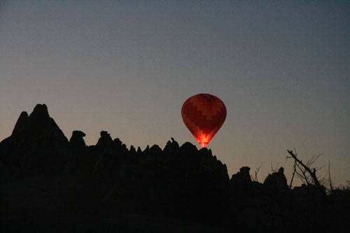 Hot Air Balloon glowing over Cappadocian landscape